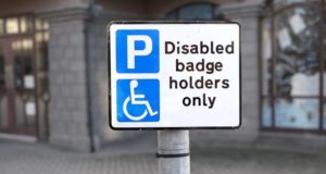 Blue badge sign featuring a blue parking sign and a blue wheelchair sign beside text disabled badge holders only