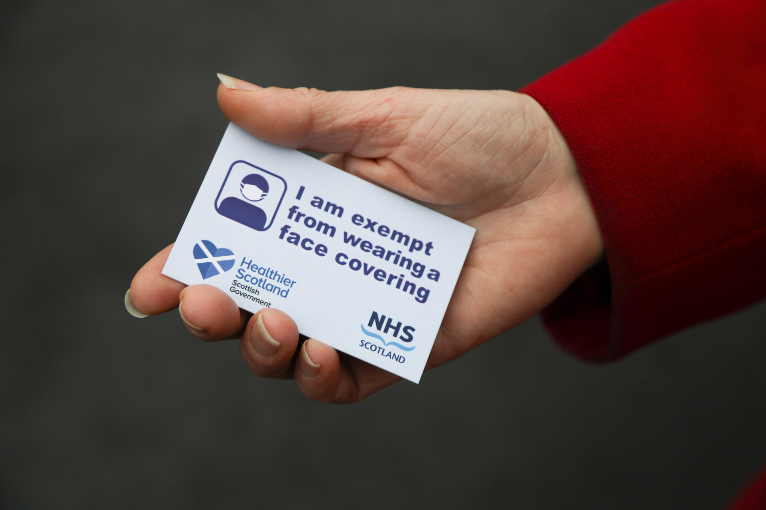 A person holding the Scottish Government face covering exemption card featuring healthier Scotland logo and NHS Scotland logo